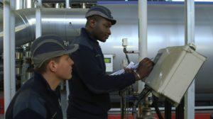 Photo de 2 apprentis devant une machine afanem